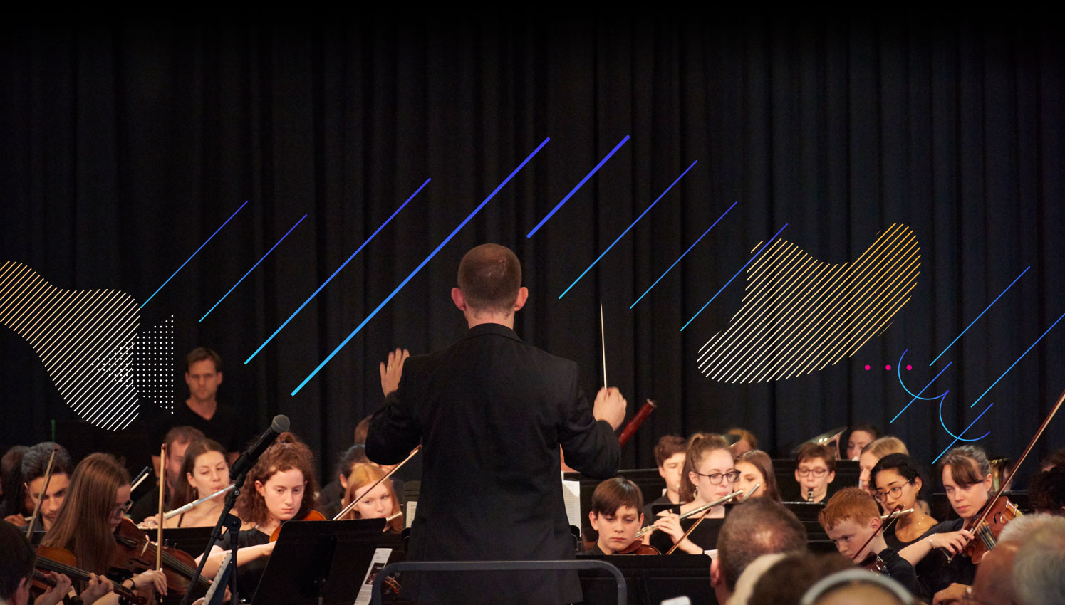 Conductor stood in front of youth orchestra
